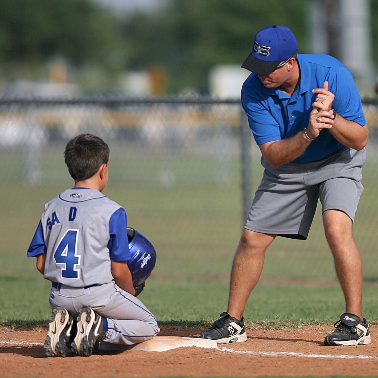 coach with child during baseball practice
