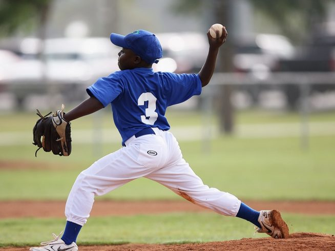 boy pitching baseball during active game