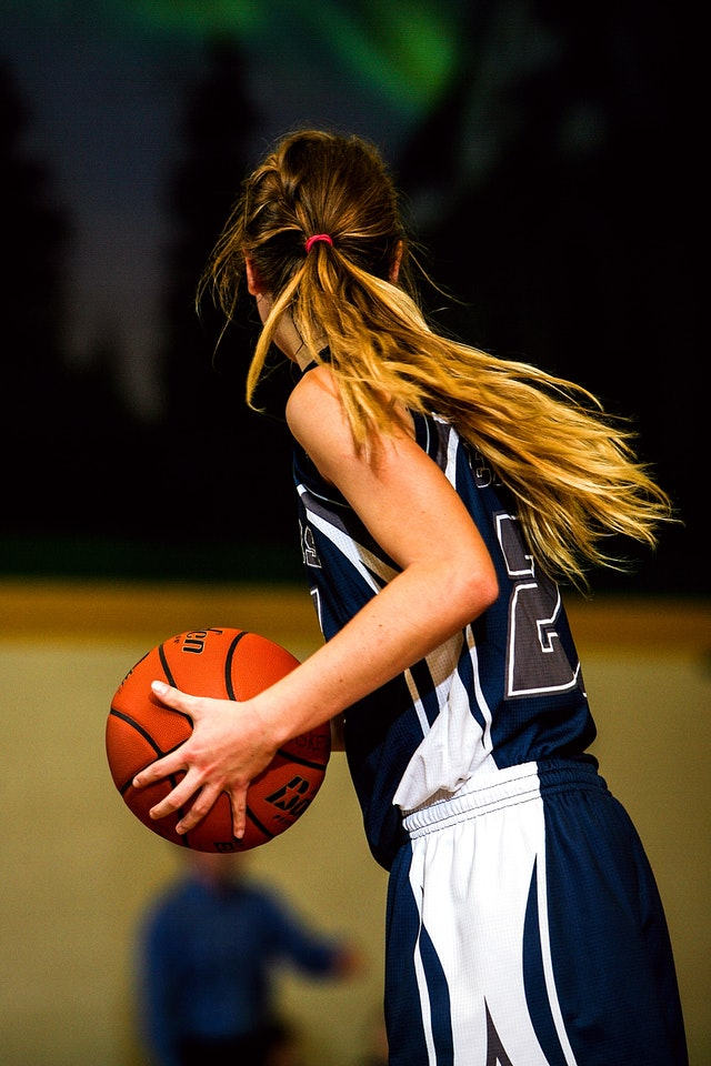 girl with baskeball in hands in middle school basketball game
