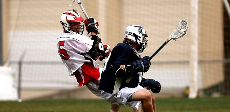 2 men playing lacrosse with helmets action of pivoting