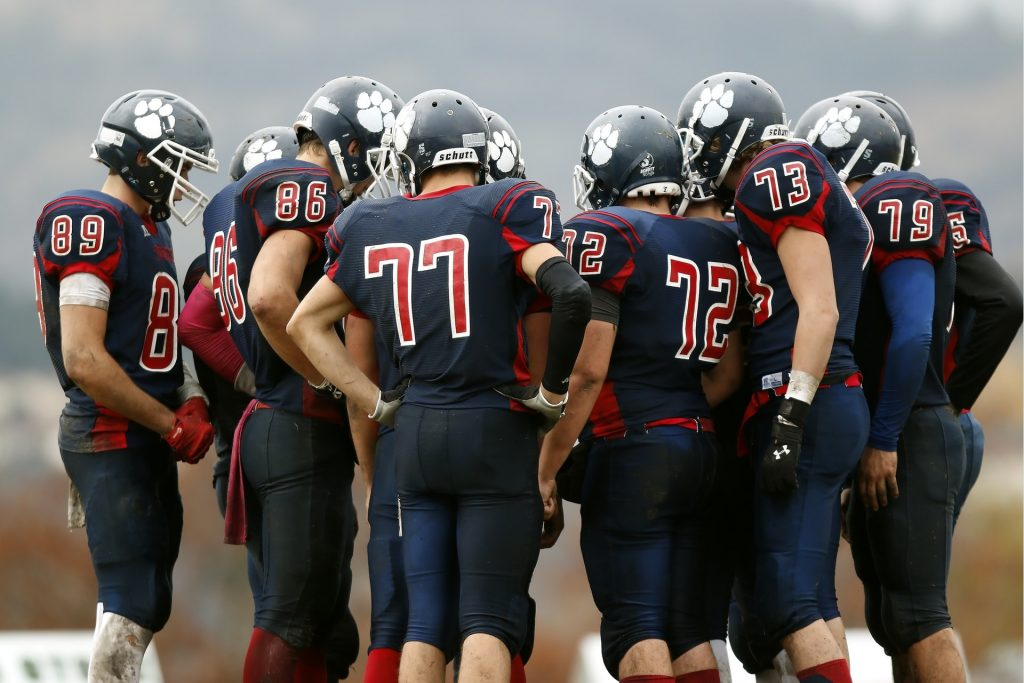 group of highschool football players standing in a huddle