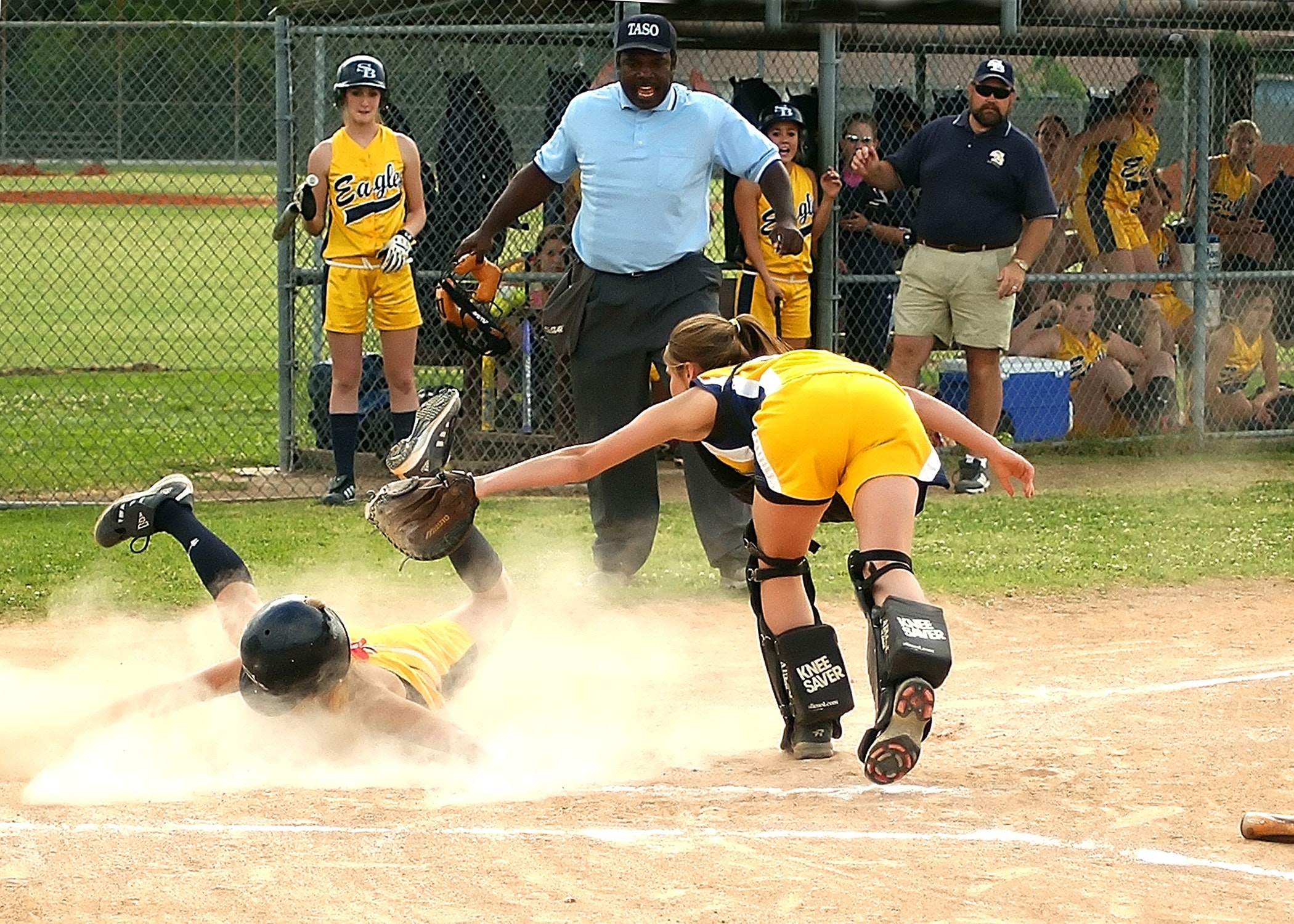 girls playing softball with ref sliding actively