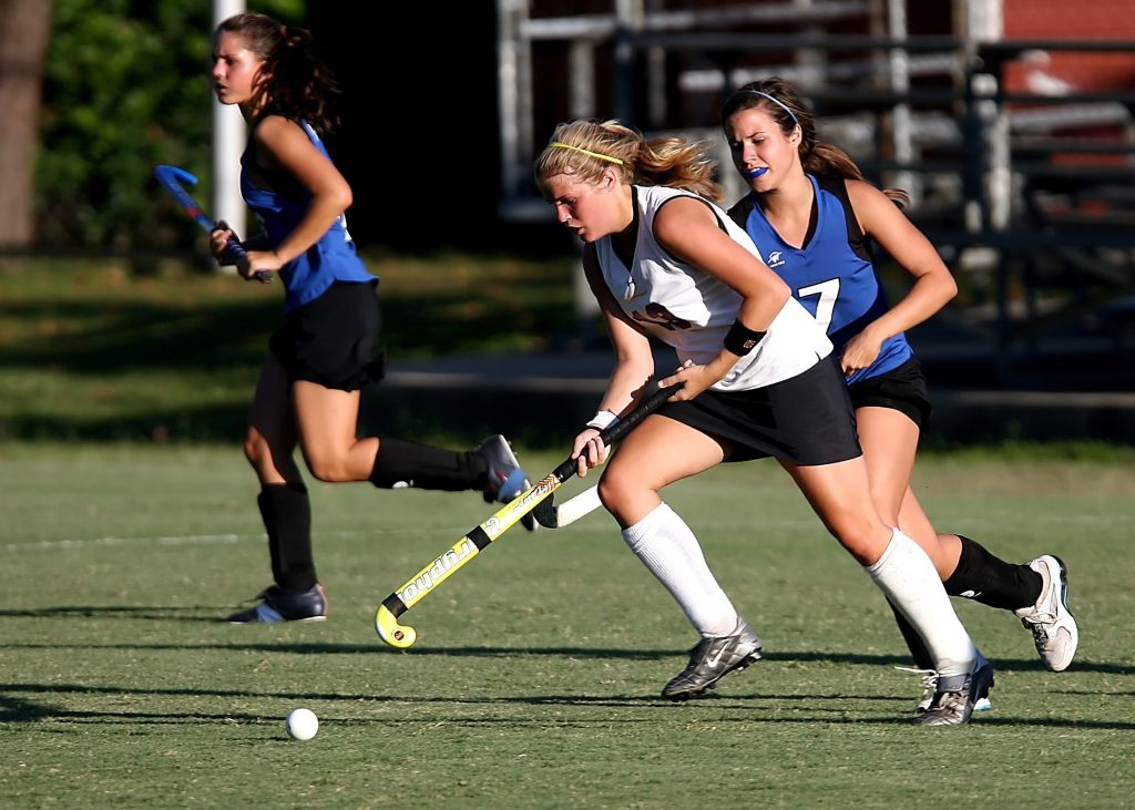 field hockey game at highschool with 2 women running