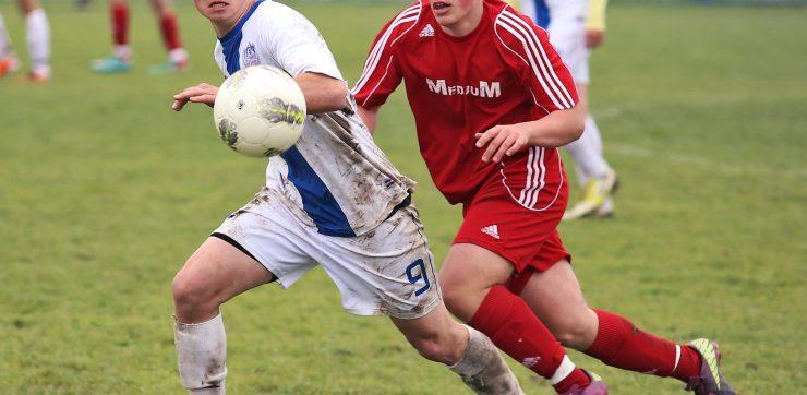 2 high school boys running playing soccer