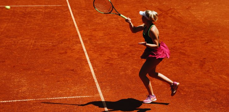 woman playing tennis on a dirt court with ball in air